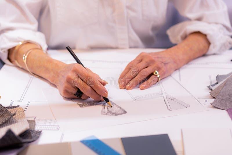 Kubka strzał starzenie się żeński szef pracuje na projekta rysunku zdjęcia stock