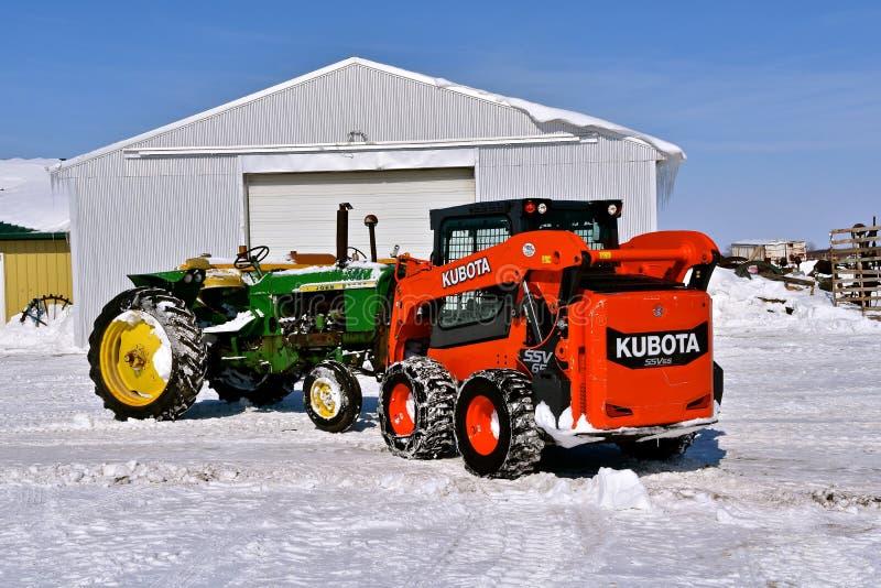Kubota som skjuter en John Deere traktor arkivfoton