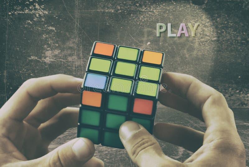 Kubus in de handen van een mens tegen de achtergrond van een uitstekende muur Speel het spel royalty-vrije stock afbeeldingen
