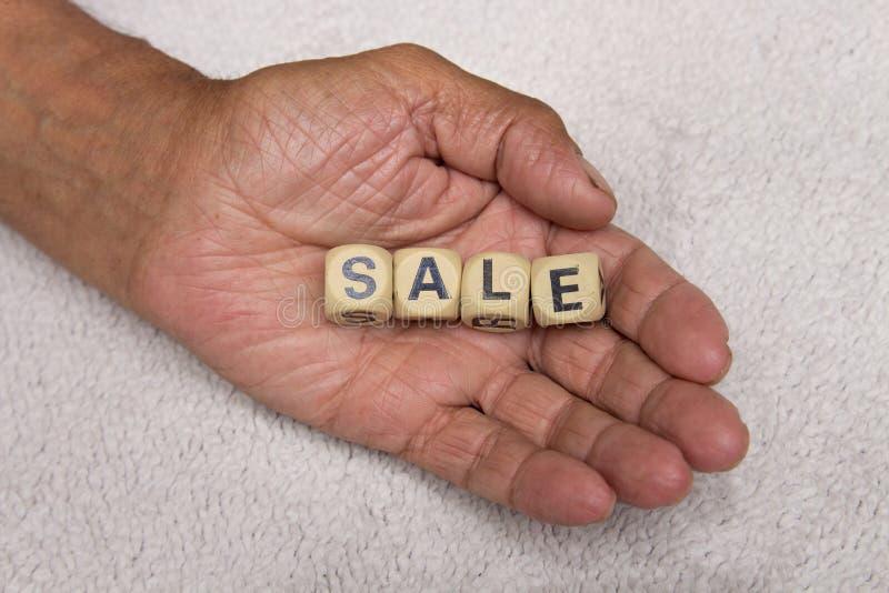 Kubussen met de woordenverkoop in de handen van een bejaarde persoon Het concept verkoop stock afbeeldingen