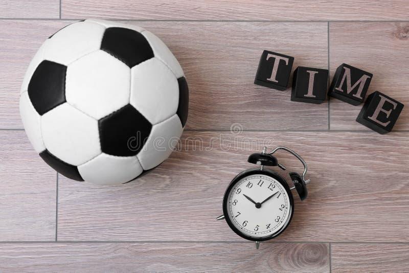 Kubussen met wekker en voetbalbal stock afbeelding
