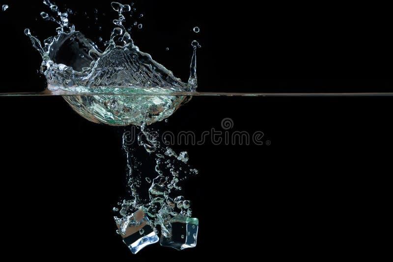 Kubussen van ijs in water met plons royalty-vrije stock afbeelding