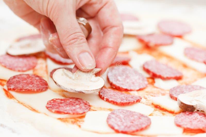 Kucbarska kładzenie pieczarka nad mozzarellą i salami na surowej pizzy zdjęcie stock