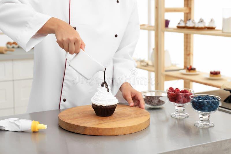 Kucharka cukierniczka polewa sos czekoladowy na babeczkę przy stole w kuchni zdjęcie stock
