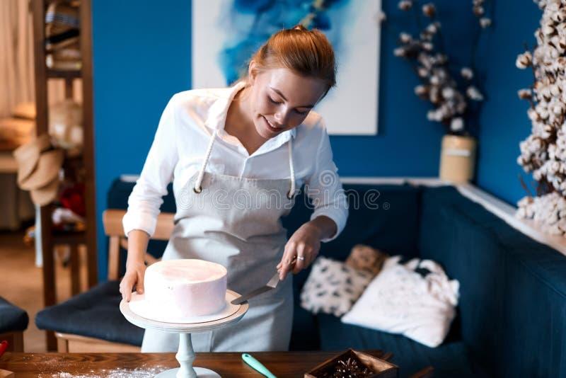 Kucharka lub piekarka w białej koszuli, białe fartuchy przy stole w studio obrazy stock