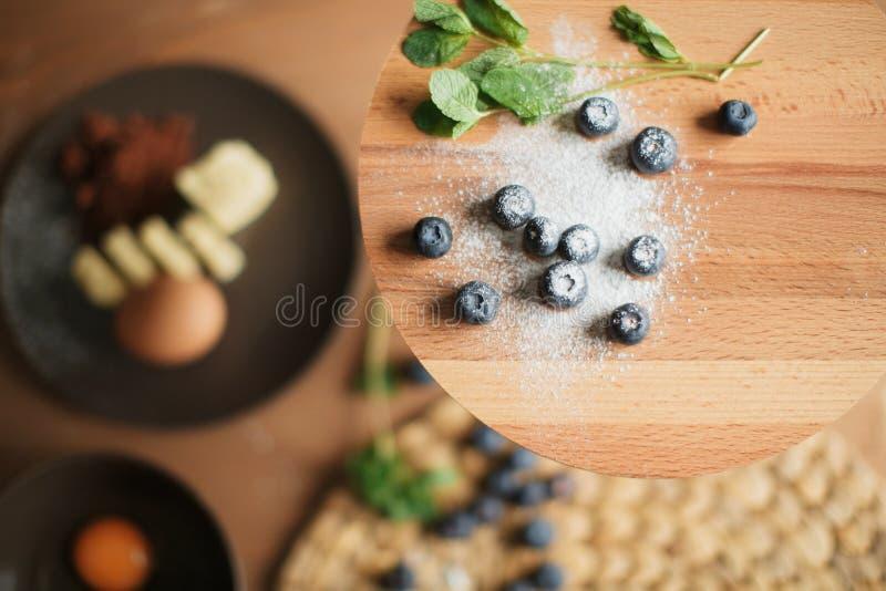 Kuchen auf dem Tisch kochen und Kuchenbestandteile backend stockbild