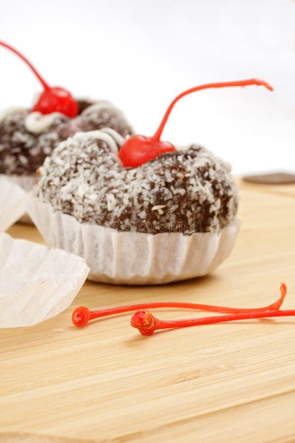 Kuchen in den Kokosnusschips und -kirschen stockbild