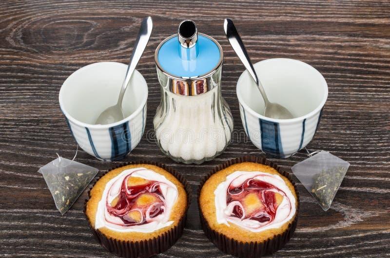 Kuchen, leere Schalen-, Tee- und Zuckerschüssel auf Tabelle lizenzfreie stockbilder