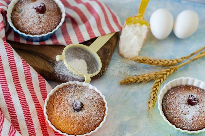 Kuchen mit cerries auf einer Tabelle in den kleinen Porzellanschalen Es gibt stockfotografie