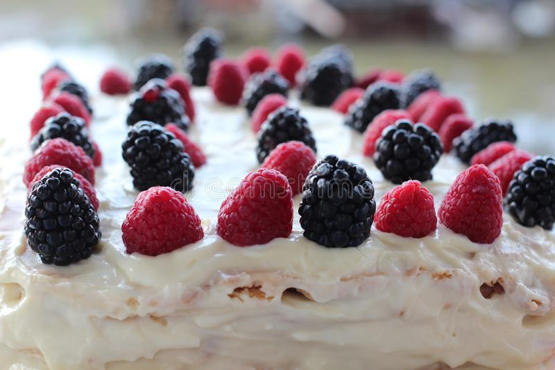 Kuchen mit gepeitschter weißer Creme, neuem Blaubeeren-, Brombeere und Himbeereabschluß oben stockbild