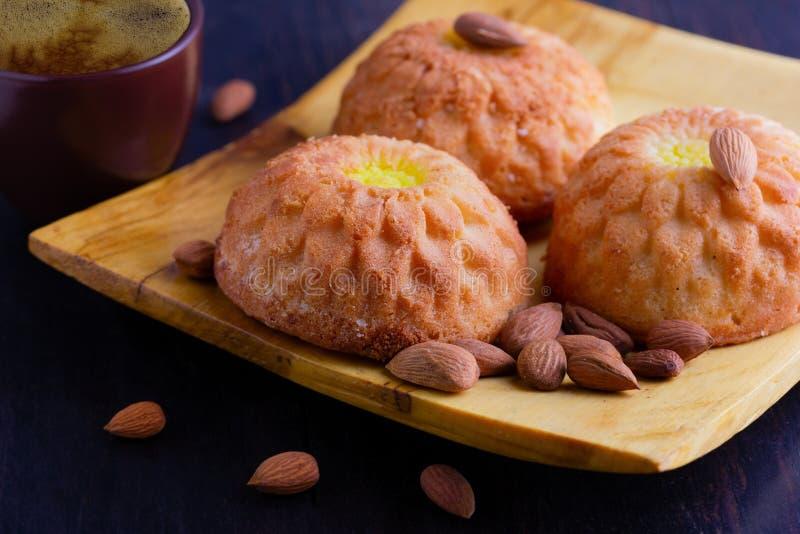 Kuchen, Muffins und Mandeln auf einer hölzernen Platte Espressokaffee in einer braunen keramischen Schale lizenzfreies stockbild
