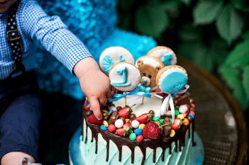 Kuchen und Babyhand feiern 1 Jahre stockfotos