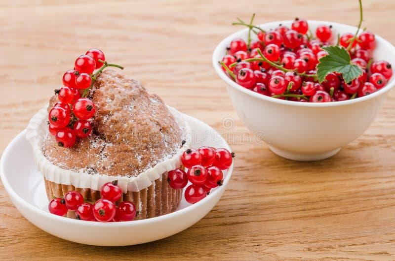 Kuchen wird mit Beeren verziert und rote Johannisbeere in einer weißen Schüssel/in einem Kuchen wird mit Beeren und roter Johanni stockbilder