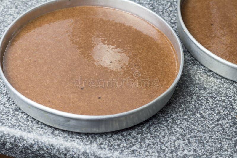 Kuchenform mit Schokoladenteig auf die Küchenarbeitsplatteoberseite lizenzfreies stockbild