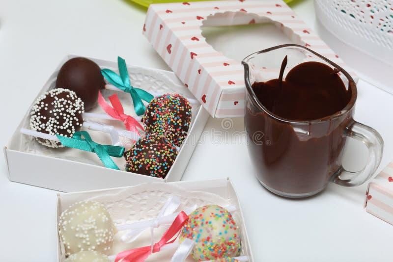 Kuchenknalle verziert mit einem Bogen der Borte, verpackt in einer Geschenkbox Sind in der N?he Schalen geschmolzene Schokolade stockbilder