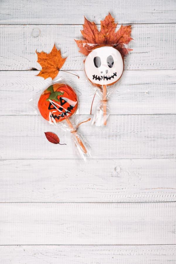 Kuchenknalle wie Geist und Kürbis für Halloween auf dem Holztisch lizenzfreie stockbilder