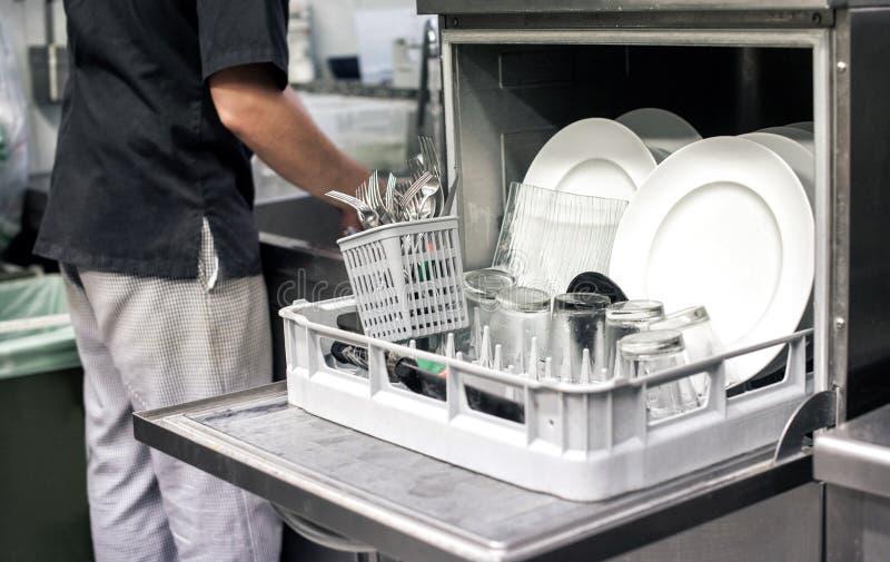 Kuchenna ręka z otwartym zmywarka do naczyń obraz stock