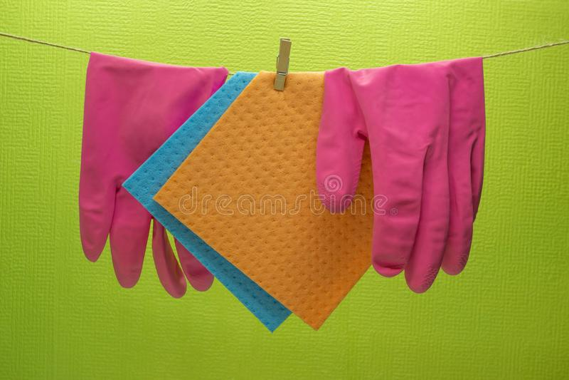 Kuchenne gąbki i gumowe rękawiczki wiesza na arkanie obraz stock
