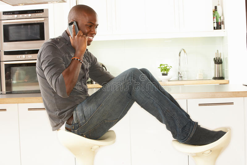 kuchennego mężczyzna telefonu relaksujący siedzący target1531_0_ zdjęcie royalty free