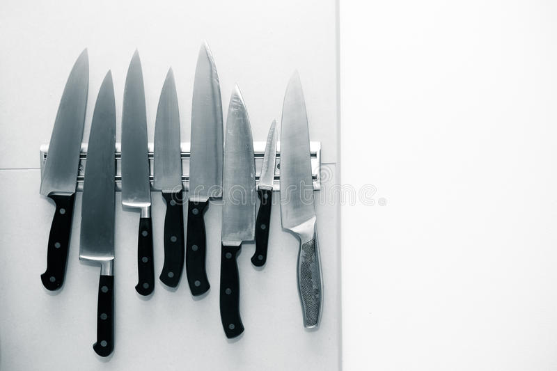 Kuchenni noże ustawiający na magnesie na zaświecają ścianę dla tła T fotografia stock