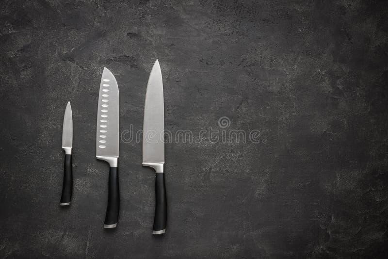 Kuchenni noże Ustawiający na zmroku kamienia tle obrazy stock