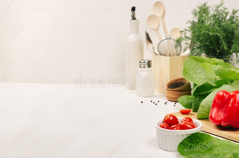 Kuchenny biały wnętrze z surową świeżą zieloną sałatką, czerwoni czereśniowi pomidory, kitchenware na miękkim białym drewno stole zdjęcia stock