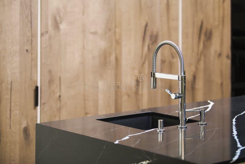 Kuchenny faucet, nowożytna kuchnia w loft stylu, czerń marmuru stół, drewniana luksusowa kuchnia zdjęcia stock