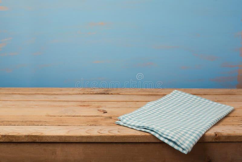 Kuchenny tło z tablecloth na pustym drewnianym stole nad malującą błękit ścianą obraz stock