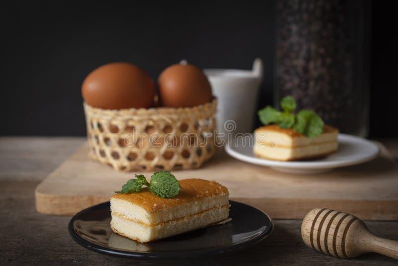Kuchenplatz der Schicht sind mit Vanillegeschmack auf Schwarzblech auf dem Holztisch dort weiße Platte und Kaffeebohne in den Gla lizenzfreies stockfoto