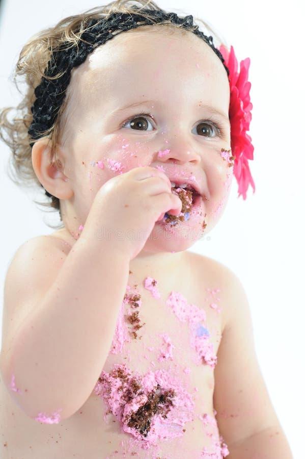 Kuchenzertrümmerntrieb: Unordentliches Baby, das Geburtstagskuchen isst! stockfotografie