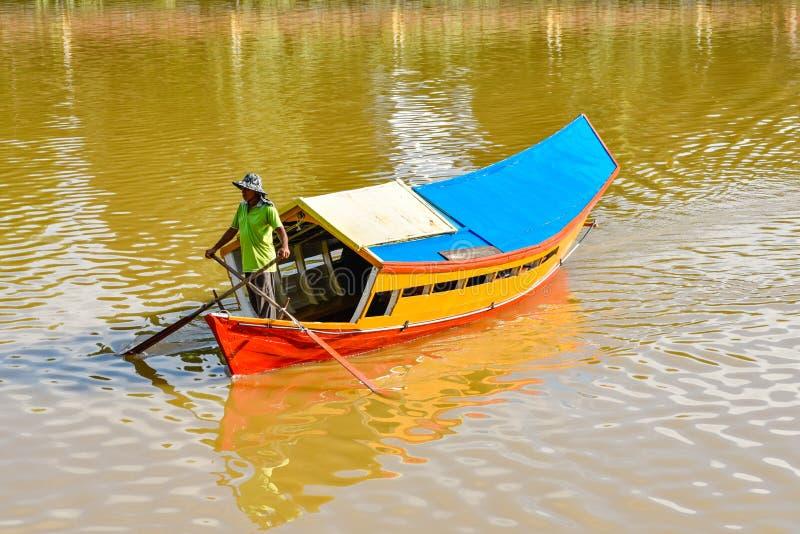 Kuching: Barcaiolo che attraversa il fiume con la sua barca fotografie stock libere da diritti
