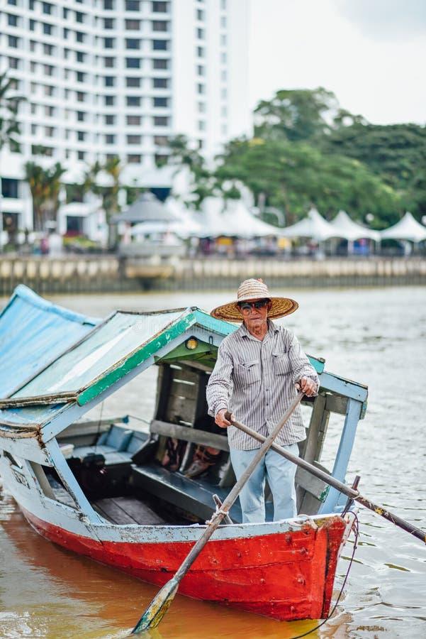 Kuching: Barcaiolo che manovra la sua barca di servizio che attraversa il fiume di Sarawak fotografie stock