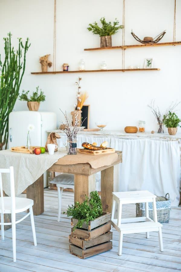Kuchnia w wieśniaka stylu w lecie Wiosny światło textured kuchnię z starym fridge, drewniany stół Drewniana taca z wazą, fotografia stock
