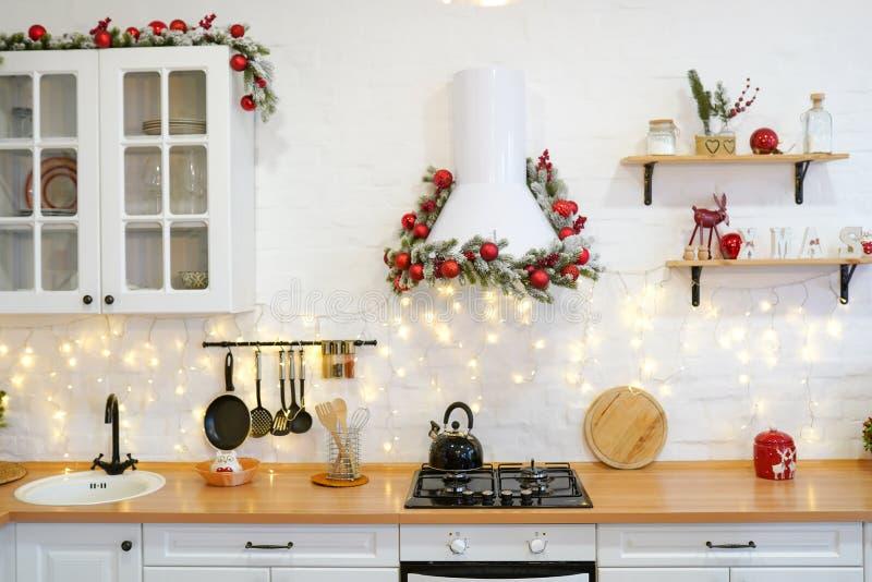 Kuchnia zimowa z czerwonymi ozdobami, stolik i naczynia do gotowania w święta obrazy stock