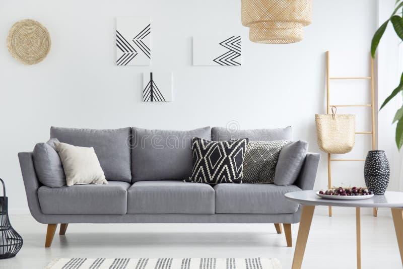 Kuddar på den gråa soffan i den vita vardagsruminre med affischer, lampan och trätabellen Verkligt foto arkivbild