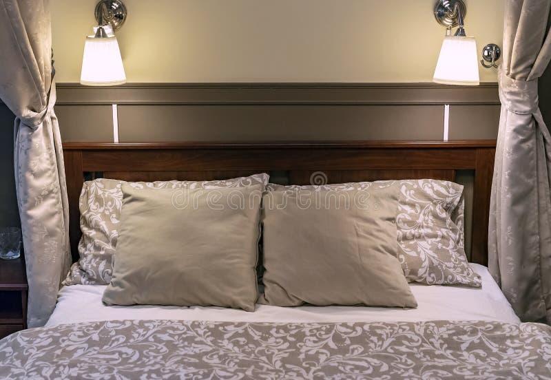 Kuddar på en säng i ettstil sovrum Inre av ett klassiskt sovrum i beigea signaler royaltyfri foto