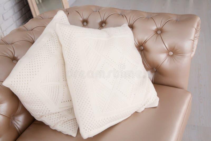 Kudde för vit fyrkant på lädersoffan arkivbild