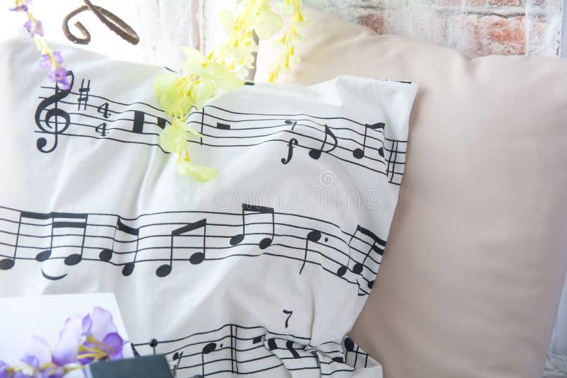Kudde med musikaliska anmärkningar på fönsterbrädan med blommor Bakgrund för tegelstenvägg med konstgjorda blommor royaltyfria foton