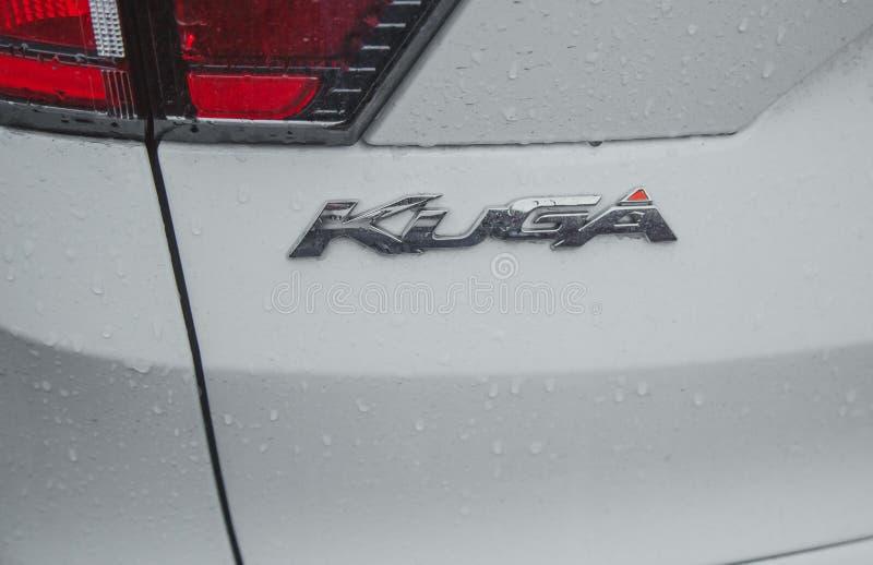 Kugainschrijving op een witte auto Ford Kuga met regenkappen stock foto's