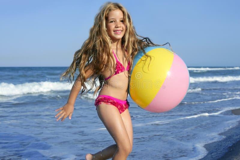 Kugel des kleinen Mädchens des Strandes, die in den Ferien spielt lizenzfreies stockfoto