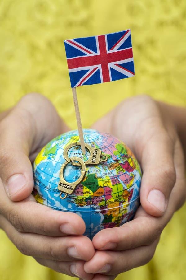 Kugel mit der Flagge von Großbritannien und von Metall fesselt mit der Wörter Freiheit mit Handschellen lizenzfreie stockfotografie