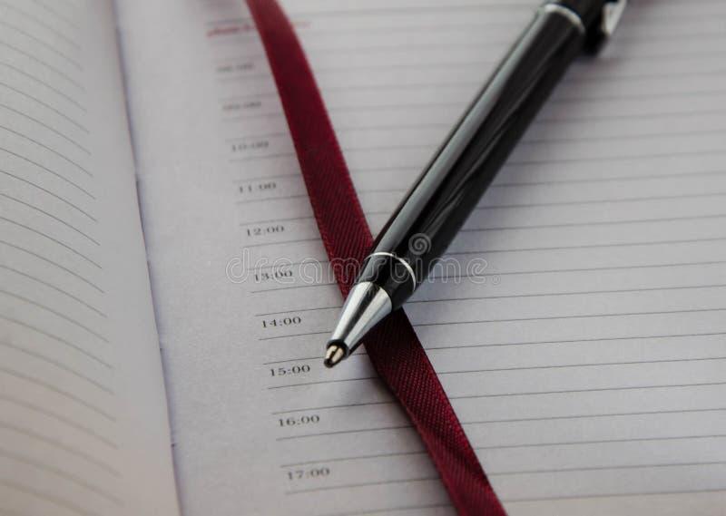 Kugelschreiber auf dem Hintergrund eines Notizbuches mit rotem Bookmark lizenzfreie stockfotografie