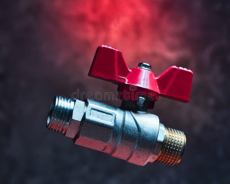 Kugelventil auf dem Hintergrund einer Betonmauer Mystisches rotes Licht stockfotografie