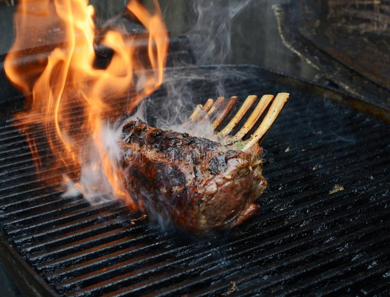 Kugge av lammet på grillfest med flamman och rök fotografering för bildbyråer