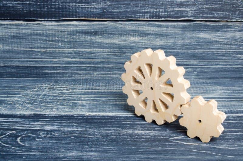 Kugghjul av den wood ställningen på en mörk träbakgrund Begrepp av teknologi och bransch som iscensätter Mekaniska delar som är t royaltyfri fotografi