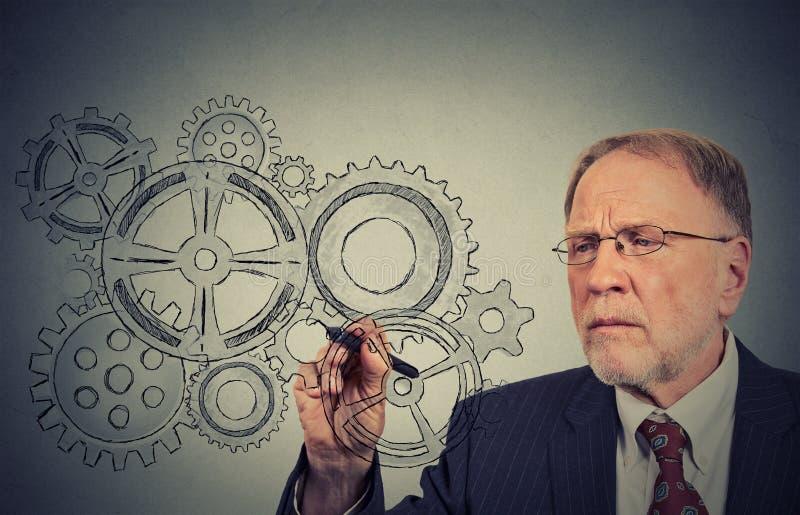 Kugghjul och idéer Tekniker- eller åldringaffärsmanledare arkivbild