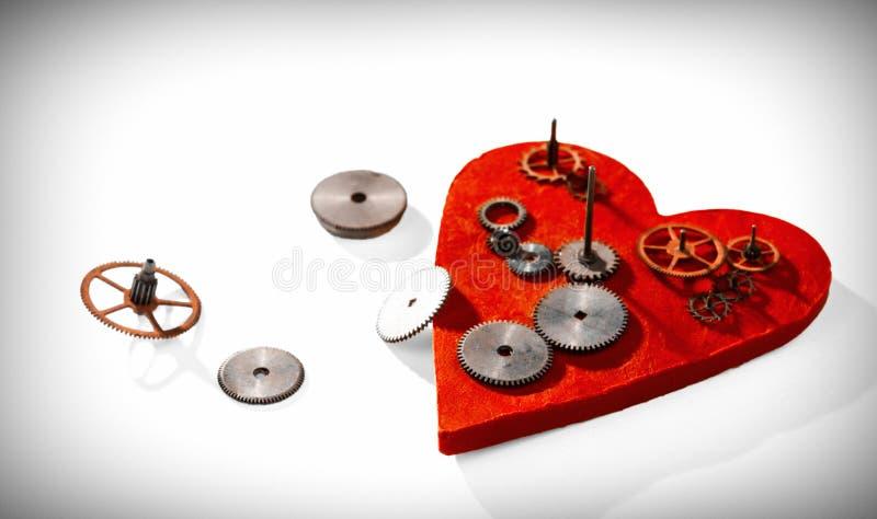 Kugghjul på bakgrunden av den röda hjärtan arkivbilder