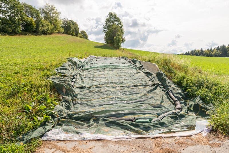 Kuilvoeder met een plastic folie in het Beierse Bos, Duitsland wordt behandeld dat stock fotografie
