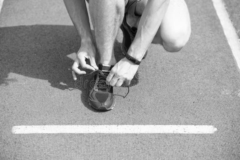 Kuje elita biegaczów jest ubranym maraton Ręki wiąże shoelaces na tenisówka, działającej powierzchni tło Ręki sportowiec zdjęcie royalty free