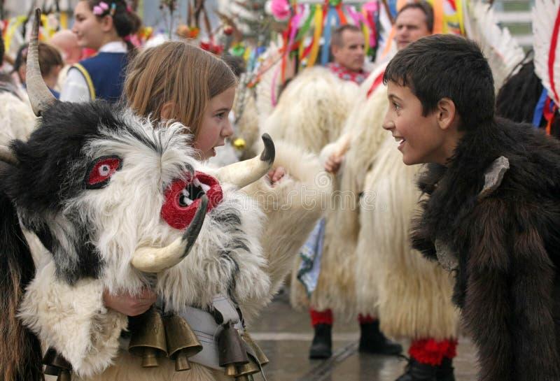 Kukeri, máscaras de los niños realiza rituales con los trajes y las campanas grandes en el festival internacional del  de Survaâ foto de archivo libre de regalías